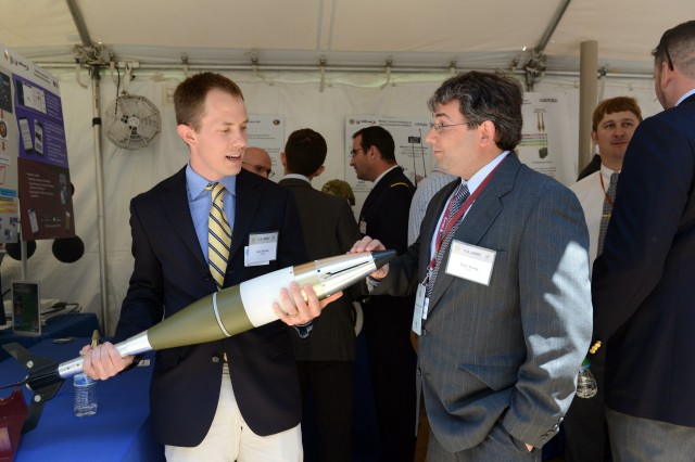 Nick Baldwin and Evan Young, researchers with the Armament Research Development and Engineering Center at Picatinny Arsenal, New Jersey, discuss the 120mm Guided Enhanced Fragmentation Mortar during the DOD Lab Day, May 14 at the Pentagon.