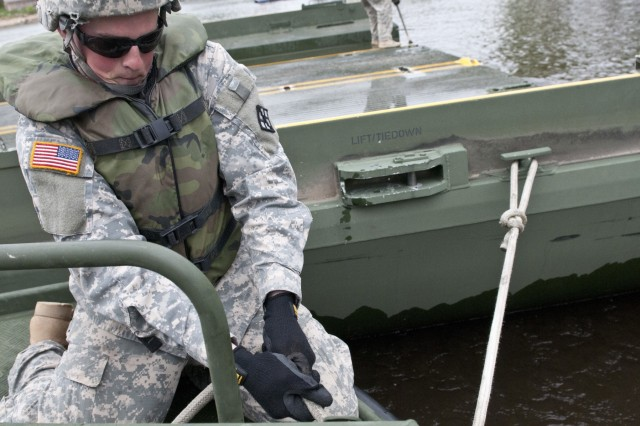 Pfc. Brandon Mcleod, bridge crew member with the 459th Engineer Company (Multi-role Bridge) out of Bridgeport, W. Va., pulls a rope tight to secure a bridge erection boat to a improvised ribbon bridge bay during Warrior Exercise 15-02. The 459th Eng. Co., augmented by the 299th and 310th Engineer Companies (Multi-role Bridge) conducted bridging operations on the Mississippi River in La Crosse, Wis., as their culminating operation of the exercise. (U.S. Army photo by Staff Sgt. Debralee Best)