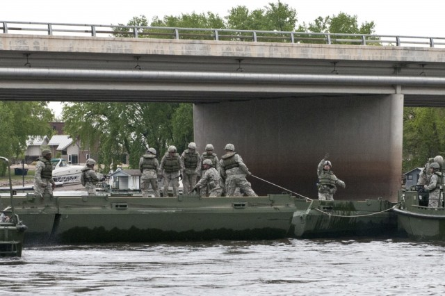 Bridge crew members with the 459th Engineer Company (Multi-role Bridge) out of Bridgeport, W. Va., augmented by the 299th, out of Fort Belvior, Va., and 310th, out of Fort A.P. Hill, Va., Engineer Companies (Multi-role Bridge) push improvised ribbon bridge bays together with bridge erection boats on the Mississippi River in La Crosse, Wis., as their culminating operation of the Warrior Exercise 15-02. (U.S. Army photo by Staff Sgt. Debralee Best)