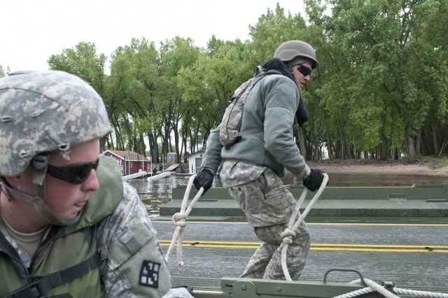 Pvt. Chad Carley, bridge crew member with the 299th Engineer Company (Multi-role Bridge) out of Fort Belvoir, Va., brings ropes aboard an improvised ribbon bridge bay to secure it to a bridge erection boat to during Warrior Exercise 15-02. The 459th Eng. Co. out of Bridgeport, W. Va., augmented by the 299th and 310th, out of Fort A.P. Hill, Va., Engineer Companies (Multi-role Bridge) conducted bridging operations on the Mississippi River in La Crosse, Wis., as their culminating operation of the exercise. (U.S. Army photo by Staff Sgt. Debralee Best)