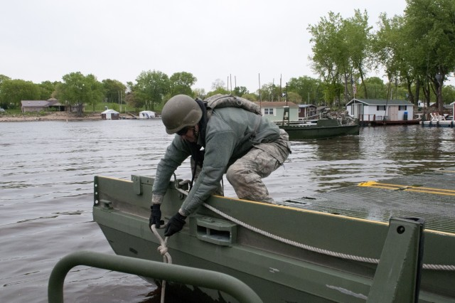 Pvt. Chad Carley, bridge crew member with the 299th Engineer Company (Multi-role Bridge) out of Fort Belvoir, Va., secures an improvised ribbon bridge bay to a bridge erection boat to move the bay into place during Warrior Exercise 15-02. The 459th Eng. Co. out of Bridgeport, W. Va., augmented by the 299th and 310th, out of Fort A.P. Hill, Va., Engineer Companies (Multi-role Bridge) conducted bridging operations on the Mississippi River in La Crosse, Wis., as their culminating operation of the exercise. (U.S. Army photo by Staff Sgt. Debralee Best)