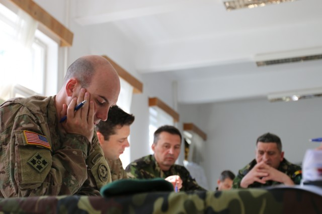 Military officials from the U.S., British and Romanian armies unite to conduct a ROC drill in preparation for the Sarmis Training Exercise at Brasov Garrison, Romania, May 21, 2015. The Sarmis Training Exercise is an opportunity for the NATO allies to conduct joint training to strengthen interoperability during Operation Atlantic Resolve.