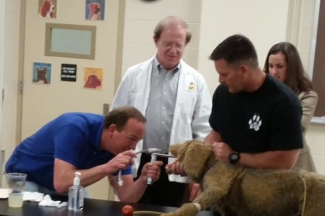 Redstone K9 unit Sgt. Billy Booth, left, and Officer Aaron Hanson, right, practice intubating a canine model under the direction of Dr. Cory Langston.