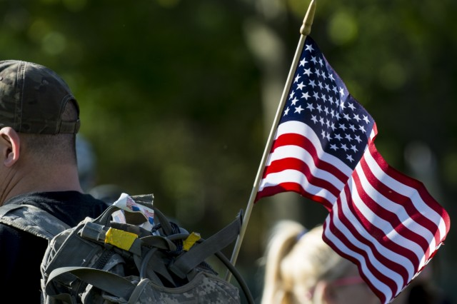 An american flag hangs on the back of a participant during the Chicago Honor the Fallen Ruck March. Approximately 450 military veterans, service members and supporters gathered for a 22-mile ruck march on May 22, just days before Memorial Day, to honor military men and women who suffer from Post-Traumatic Stress Disorder or have committed suicide. (U.S. Army photo by Sgt. 1st Class Michel Sauret)