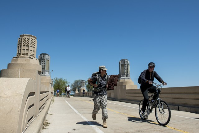 An Army staff sergeant talks to a bicyclist as she holds a solid lead during the Chicago Honor the Fallen Ruck March. Approximately 450 military veterans, service members and supporters gathered for a 22-mile ruck march on May 22, just days before Memorial Day, to honor military men and women who suffer from Post-Traumatic Stress Disorder or have committed suicide. (U.S. Army photo by Sgt. 1st Class Michel Sauret)
