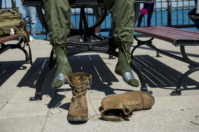 Jake Coffman, a Marine Corps veteran, takes off his boots at Navy Pier after finishing the Chicago Honor the Fallen Ruck March. Approximately 450 military veterans, service members and supporters gathered for a 22-mile ruck march on May 22, just days before Memorial Day, to honor military men and women who suffer from Post-Traumatic Stress Disorder or have committed suicide. (U.S. Army photo by Sgt. 1st Class Michel Sauret)