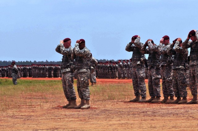 """Col. Mark Collins and Command Sgt. Maj. Ian Dames, 82nd Airborne Division Sustainment Brigade command team, don the maroon beret after removing their Army patrol caps during the All American Week 2015 Airborne Review on Fort Bragg, N.C., May 21, 2015. The donning of the beret marked the brigade's transition back to the 82nd Abn. Div. after detaching from the Division in 2008. All American Week is an opportunity for 82nd Abn. Div. paratroopers, past and present, and their families to come together and enjoy the camaraderie and celebrate being members of the All American Division. This year's All American Week theme is """"Past, Present, and Future."""" (U.S. Army photo by Staff Sgt. Adam C. Keith, 82nd Abn. Div. Sus. Bde./Released)"""