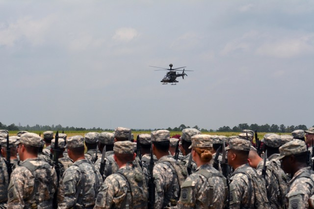 """Soldiers from the 82nd Airborne Division Sustainment Brigade watch an Army OH-58 Kiowa Warrior fly by their formation during the All American Week 2015 Airborne Review on Fort Bragg, N.C., May 20, 2015. The brigade's Soldiers replaced their Army patrol caps for the maroon beret during the review, marking the brigade's transition back to the 82nd Abn. Div. after detaching from the Division in 2008. All American Week is an opportunity for 82nd Abn. Div. paratroopers, past and present, and their families to come together and enjoy the camaraderie and celebrate being members of the All American Division. This year's All American Week theme is """"Past, Present, and Future."""" (U.S. Army photo by Staff Sgt. Adam C. Keith, 82nd Abn. Div. Sus. Bde./Released)"""