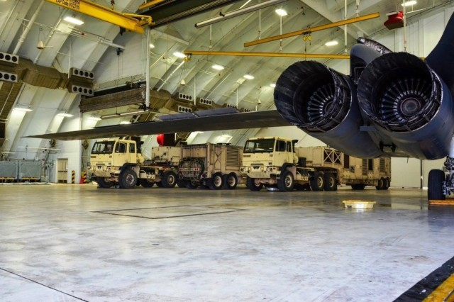 Terminal High Altitude Area Defense equipment is shown parked next to a B1B Lancer bomber in preparation for the arrival of Typhoon Dolphin on Andersen Air Force Base, Guam.