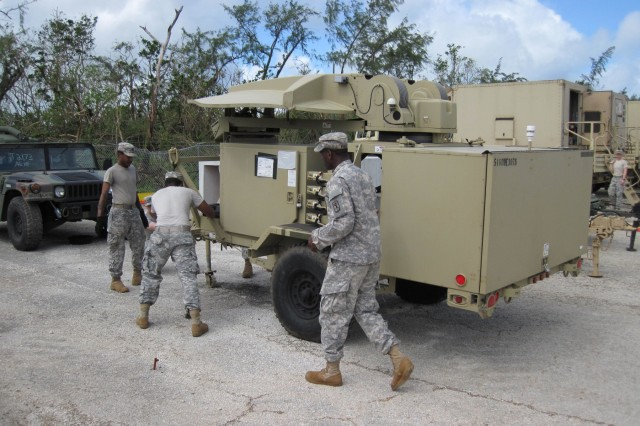 Army Spc. Paul Latimer, left, from Battery D, 2nd Air Defense Artillery Regiment, and Sgt. Jarius Bruce, middle, and Spc. Brandon Fuller, right, both from the 307th Signal Battalion emplace communications equipment after the passing of Typhoon Dolphin.