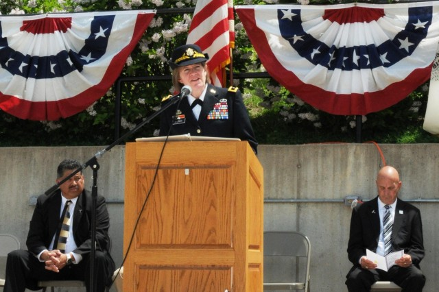 Brig. Gen. Kristin French, Joint Munitions Command, commander, provides remarks during the Hero Street Memorial Park service, May 23. Sitting on the stage behind French is 1st Ward Alderman Bob Cervantes, left, and Silvis, Illinois Mayor Tom Conrad. The park is dedicated to members of all branches of the Armed Forces and was originally established to honor the eight Mexican-American Servicemen from the small neighborhood who died while serving during World War II and the Korean War. (Photo by Tony Lopez, JMC Public Affairs)