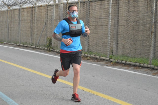 SUWON AIR BASE, South Korea -- Chief Warrant Officer 3 Bradford Hudgins, standardizations officer with 6-52 Air Defense Artillery, crosses the finish line in a weighted vest and training mask during the second annual Run for the Fallen 5K here, May 20, 2015.  The run served as a remembrance for those killed in the wars in Iraq and Afghanistan.