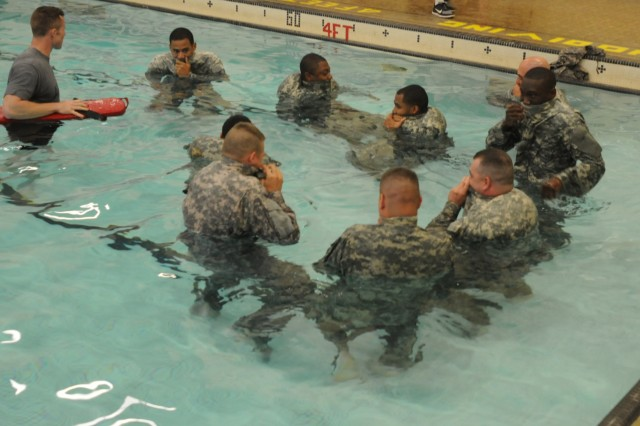 Third Sustainment Command (Expeditionary) Soldiers create flotation devices by blowing air into their Army Combat Uniforms, May 19, at Gammon Fitness Center. Water safety was one of several classes put on by 3rd ESC for Safety Stand Down Day. (U.S. Army photo by Sgt. 1st Class Gary J. Cooper, 3rd ESC Public Affairs)