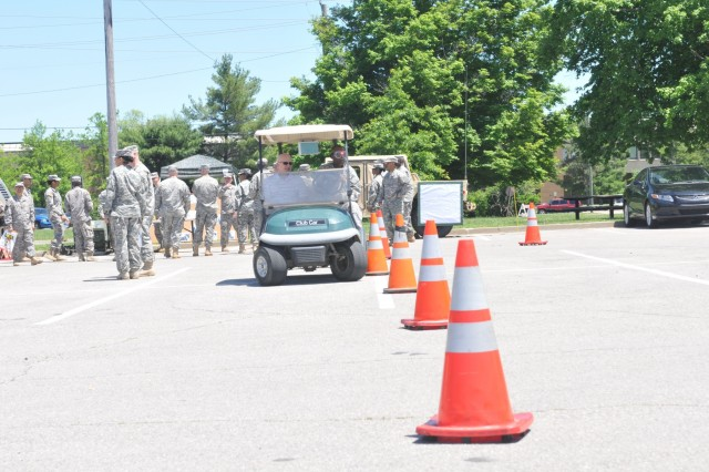 Third Sustainment Command (Expeditionary) Soldiers try to navigate through orange cones with beer goggles on while driving golf carts, May 19, outside Harris Hall. The drunk driving station was one of several safety exhibits put on by 3rd ESC for Safety Stand Down Day. (U.S. Army photo by Sgt. 1st Class Gary J. Cooper, 3rd ESC Public Affairs)