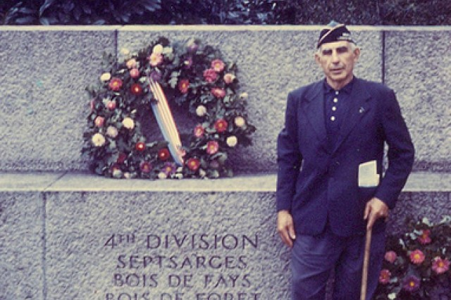 William Shemin is shown as he stands at the 4th Infantry Division monument in France: Septsarges, Bois de Fays, Bois de Foret.