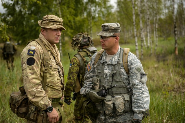 British Army Sgt. James Pierce, left, and U.S. Army Sgt. 1st Class Timothy Colon, both observer coach trainers for Exercise Saber Strike, talk about the training at Adazi Training Area, Latvia, June 12, 2014.