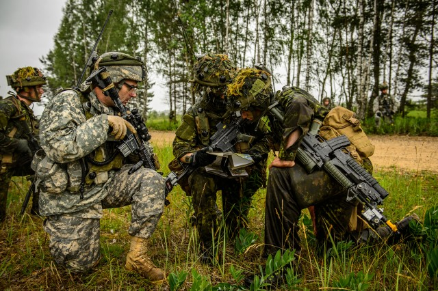 Canadian and U.S. Soldiers plan their route through a forest to an objective point during the field training portion of Exercise Saber Strike, June 16, 2014.