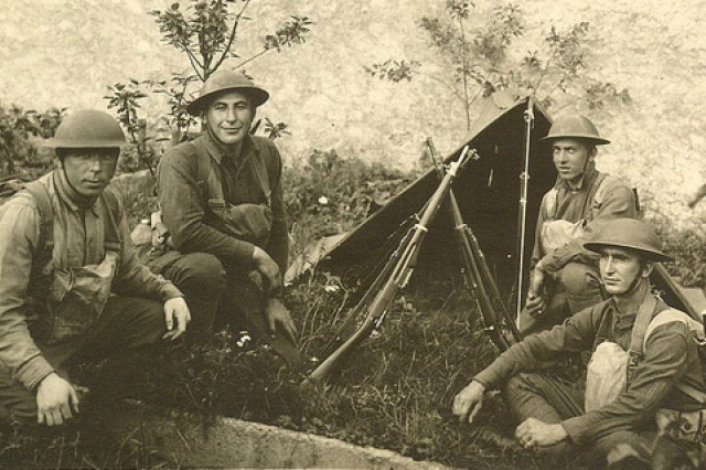 Sgt. William Shemin, kneeling second from the left, is shown as he and other Soldiers rest in the grass by a pup tent.