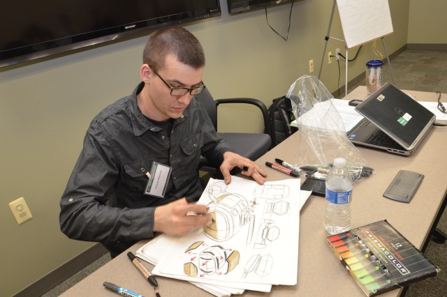 Thomas Deboves, a transportation design student from the College for Creative Studies (CCS), puts the finishing touches on a free-hand design rendering of a Mobile Protected Firepower (MPF) concept vehicle.
