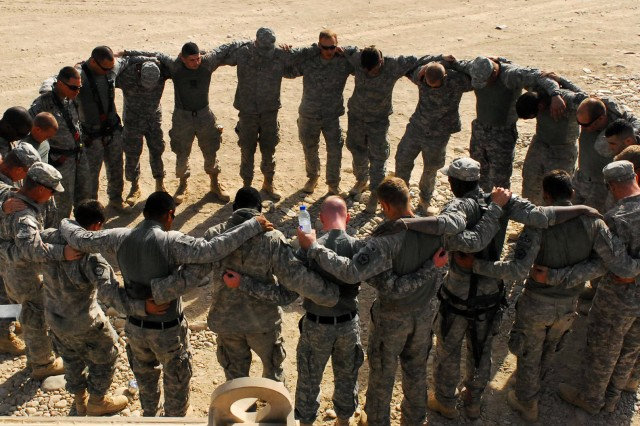 U.S. Soldiers join in to be a part of the circle, some to pray, before every mission in Kandahar, Afghanistan. The Soldiers are assigned to the 62nd Engineer Company, 4th Engineer Battalion.