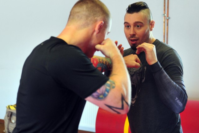 """Dan """"The Outlaw"""" Hardy, right, an accomplished veteran of the Ultimate Fighting Champion and native of Nottingham, England, demonstrates a movement technique with Staff Sgt. David Maybury, left, the 7th Civil Support Command, 21st Theater Sustainment Command master combatives trainer and a native of Tacoma, Wash., during a mixed martial arts seminar June 2 on Ramstein Airbase."""