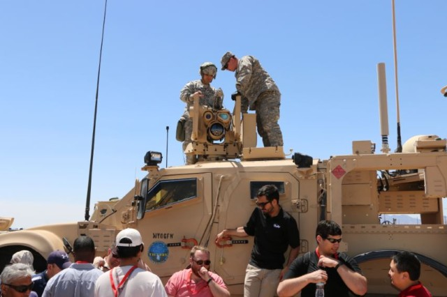 Soldiers inspect equipment on top of a prototype vehicle, which may become a future capability set. The vehicle has been fully integrated and was tested during Network Integration Evaluation 15.2 on Fort Bliss Texas.