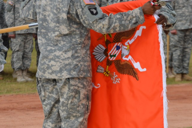 Furling the 63rd Expeditionary Signal Battalion's banner during the battalion's casing of the colors ceremony May 27 are Lt. Col. Tia Benning, 63rd ESB commander, and Command Sgt. Maj. Richard Knott, 63rd ESB command sergeant major.