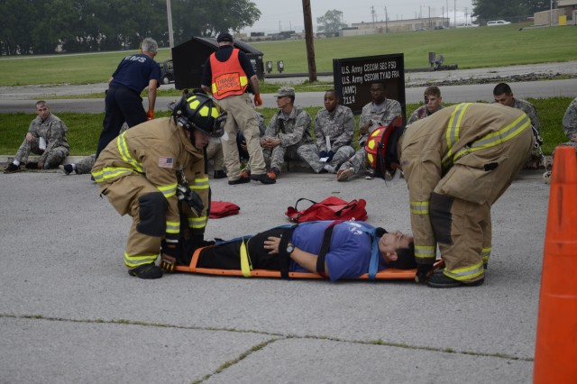 Fort Campbell firefighters Nicholas Miller and Zach Gray carry a civilian casualty outside the barracks off C Avenue so he can be triaged during the full-scale weather-related exercise Tuesday. A simulated F-3 tornado touched down, uniting Fort Campbell and local EMS, firefighters, the Red Cross and other organizaitons who responded to the notional emergency situation.