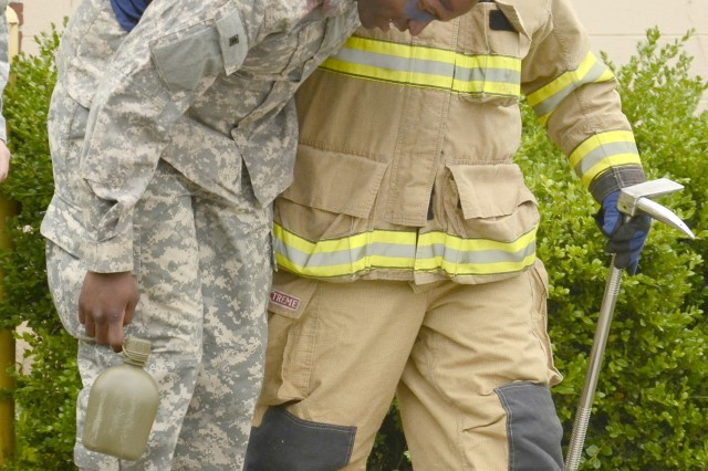 Firefighter Robert Grant, Fort Campbell Fire Department, escorts an injured Soldiers out of barracks in the vicinity of Campbell Army Airfield, Tuesday, during the full-scale weather-related exercise.