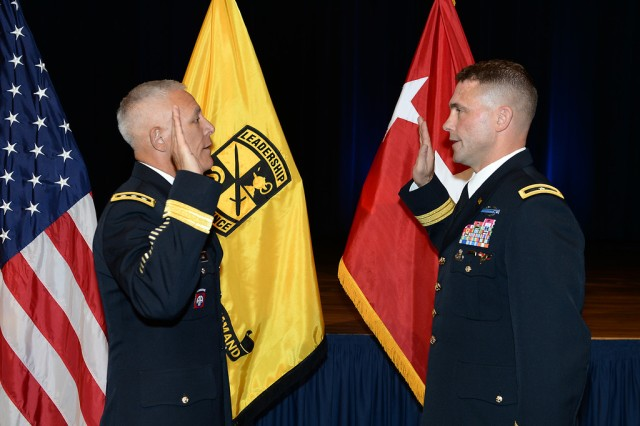 U.S. Army Lt. Gen James L. Huggins administers the oath of office to newly promoted Brigadier General Brain J. Mennes