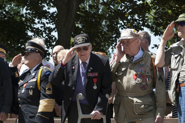 U.S. Army veterans Cpl. George Shenkle, center right, of the 508th Parachute Infantry Regiment, 82nd Airborne Division, and Sgt. Isaac Phillips, center left, of the 4th Infantry Division, salute the flag during the playing of the U.S. national anthem while at a ceremony at the Rex Combs Memorial in the Normandy region, June 4, 2015.