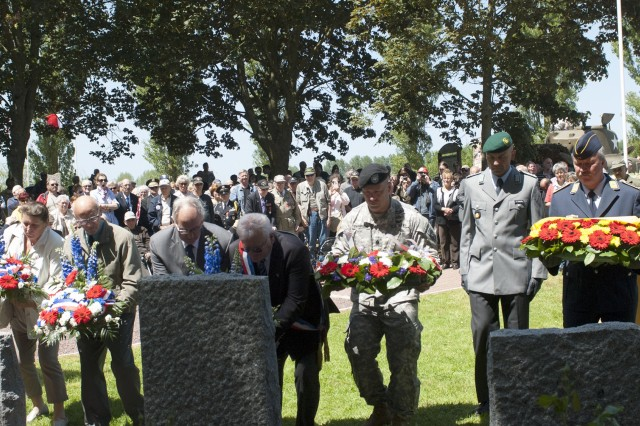 U.S. Army Lt. Col. Kurt Thompson, center, deputy commander of 2nd Brigade, 101st Airborne Division (Air Assault), places a wreath during a ceremony at the Rex Combs Memorial in the Normandy region, June 4, 2015.