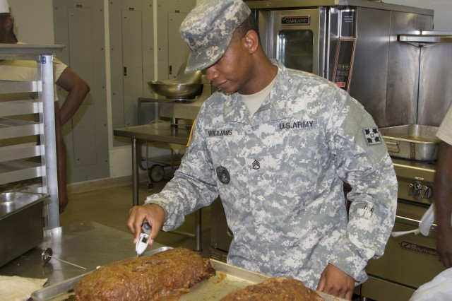 Staff Sgt. Keith Williams, dining facility manager and cook for Headquarters and Headquarters Company, 704th Brigade Support Battalion, 2nd Brigade, 4th Infantry Division, checks the internal temperature on a roast to make sure it is ready to serve to cadre and cadets at Cadet Summer Training.  Reserve Soldiers and civilian contractors will prepare and serve up to 2,200 meals per day during the Cadet Summer Training exercise.