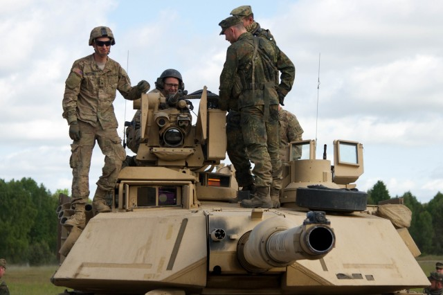 German soldiers explore an M1A2 Abrams Main Battle Tank at the Drawsko Pomorskie Training Area in Poland, June 8, 2015.