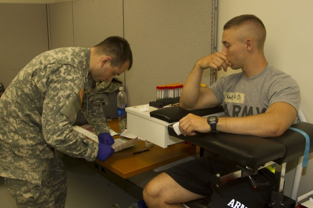 Spc. Daniel Vargas, a lab technician and phlebotomist at the Soldier Readiness Program site, signs and dates container labels after drawing blood from a cadet at the 2015 U.S. Army Reserve Officers' Training Corps Cadet Summer Trainingto ensur the patient's personal information is correct.
