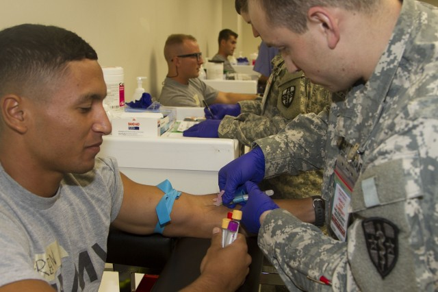 Spc. Daniel Vargas (right), a lab technician and phlebotomist at the Soldier Readiness Program site, prepares to draw blood from a cadet at the 2015 U.S. Army Reserve Officers' Training Corps Cadet Summer Training. Some of the blood tests will include HIV, MMR, Varicella and Hepatitis testing. This will be a required station for both initial entry cadets as well as cadets attending the Cadet Leader Course.