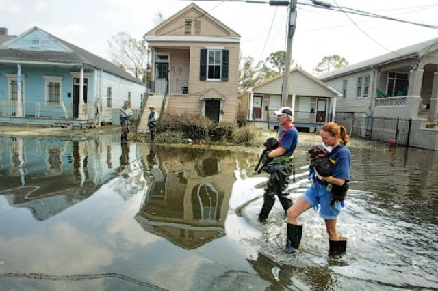 Animal rescuers walk down a flooded street carrying two dogs they had rescued in New Orleans, Louisiana, after Hurricane Katrina hit the Gulf Coast.