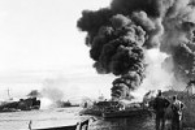 Several ships explode while Soldiers from Schofield Barracks load ammunition in support of Operation Forager on May 21, 1944. Most of the Soldiers were from the African-American 29th Chemical Decontamination Unit. A memorial ceremony was held on the tragedy's anniversary.
