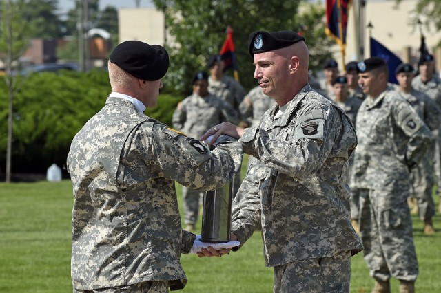 Brig. Gen. Frank W. Tate receives brass cannister from the round that was fired upon his arrival to the 101st Airborne Division (Air Assault) during his Honor Eagle ceremony marking his departure from Fort Campbell, Ky., June 11.