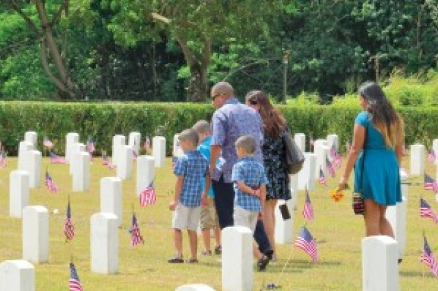 Families visit the post cemetery throughout the day.
