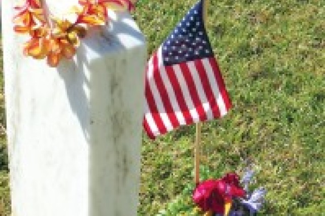 A gravesite is honored with a flag and lei.