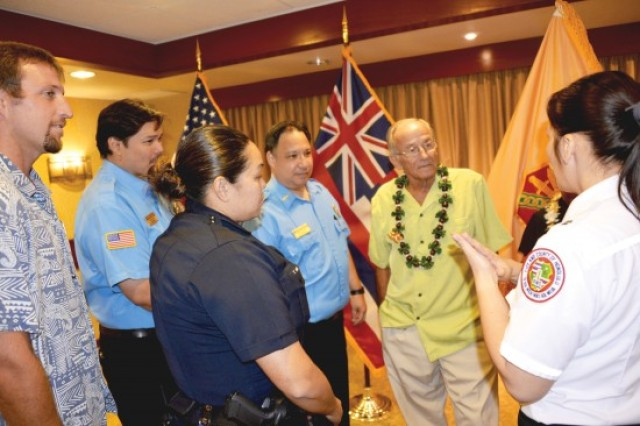 George Adkins, 2nd from right, listen as members of the Hale Koa Hotel staff, the Honolulu Police Department and the Honolulu Emergency Medical Services Department talk about the processes they all went through while aiding Adkins after his went into a cardiac arrest on May 13 at the Hale Koa Hotel.