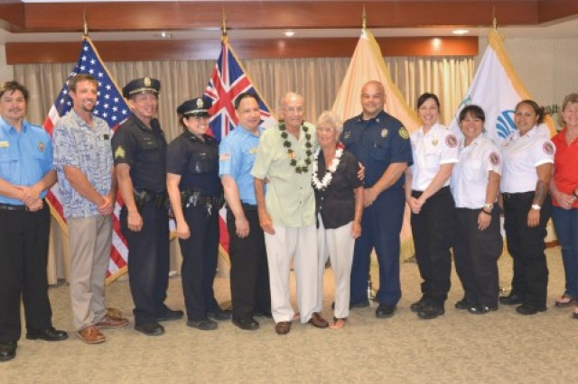 George Adkins and Sue Elliot, center, pose with the 10 first responders who teamed up to aid in Adkins' recovery after he went into a cardiac arrest at the Hale Koa Hotel's Barefoot Bar on May 13. Adkins met with the first-responders, members of the hotel staff, the Honolulu Police and Fire Departments and the Honolulu Emergency Medical Services department, on May 26, to personally thank them for the great job they did in saving his life.