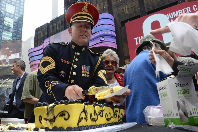 Master Sgt. Marcus Truelove with the U.S. Army Band hands out birthday cake to members of the public during a celebration in New York's Times Square for the Army's 240th birthday.