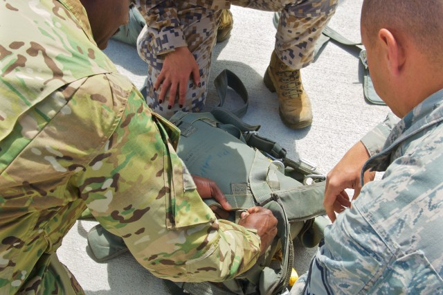 Military personnel, from the Latvian National Armed Forces, U.S. Army and Air Force inspect equipment during joint airborne training operations at Lielvarde Air Base, Latvia, June 15, 2015.