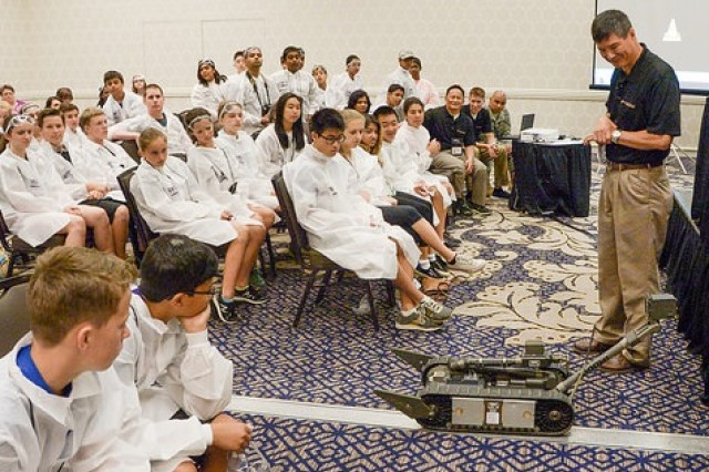 RDECOM Executive Deputy Jyuji Hewitt, right, demonstrates the Packbot robot to middle school students from across the nation during the eCYBERMISSION National Judging and Educational Event taking place June 15-19.