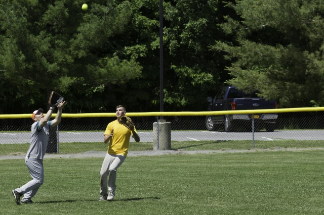Capt. Michael Jones (L) and Spc. Tyler Carman (R), outfielders for the Commando softball team, move into position to catch a fly ball during the 10th Mountain Division (LI) Mountainfest sports day June 17 at the Magrath Sports Complex softball fields. Jones and Carman are both assigned to 2nd Brigade Combat Team. Every year, teams from all the brigades and the Air Force squadron stationed on Fort Drum compete in various team sports to vie for Commander's Cup.