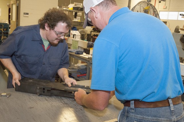 Cody Bryant, left, and Corby Tinney inspect the 324th M2 receiver ever produced. The weapon arrived at Anniston Army Depot to be converted to a M2A1 in May.