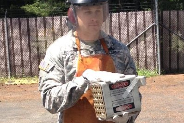 Sgt. John Kohrdt from the 707th Explosive Ordnance Disposal (EOD) Company carries a flare magazine to a disposal area during airfield training.
