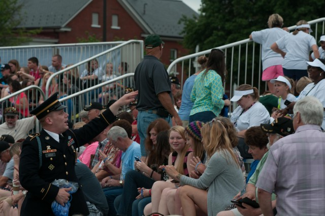A Soldier from the 3rd U.S. Infantry Regiment (The Old Guard), interacts with the audience during a Twilight Tattoo performance on Summerall Field, Joint Base Myer Henderson-Hall, Va., June 17, 2015. Twilight Tattoo is hosted by the U.S. Army Military District of Washington and is an hour-long pageant, which showcases the U.S. Army through Old Guard Soldiers and The U.S. Army Band.